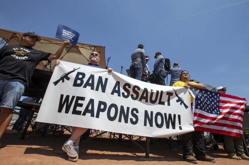 Demonstrators hold a banner calling for a ban on assault-style weapons ahead of President Trump's visit to El Paso, Texas, on Wednesday. (AP Photo/Andres Leighton)