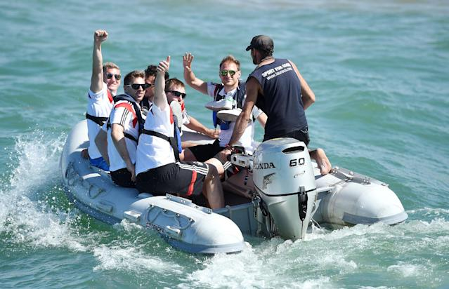 German national soccer players Bastian Schweinsteiger, background left, goalkeeper Ron-Robert Zieler, Per Mertesacker and Benedikt Hoewedes, right, ride in a boat in Santo Andre near Porto Seguro, Brazil, Tuesday, June 10, 2014. The German team got some motivation help from explorer and adventurer Mike Horn during a sailing outing near their camp on Brazil's Atlantic coast. (AP Photo/Markus Gilliar, pool)
