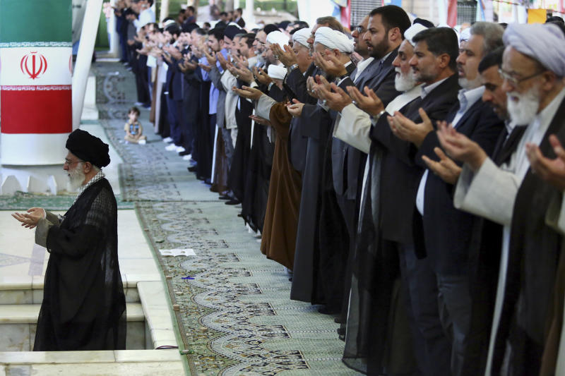 In this picture released by an official website of the office of the Iranian Supreme Leader Ayatollah Ali Khamenei, Khamenei, left, leads his sermon of Eid al-Fitr prayer, marking the start in Iran of the Eid al-Fitr holiday at the end of the holy month of Ramadan at the Tehran University campus in Tehran, Iran, Friday, Aug. 9, 2013. Khamenei lashed out at the Unites States, saying America is not a good mediator in Mideast peace talks because it allegedly sides with Israel. (AP Photo/Office of the Iranian Supreme Leader)