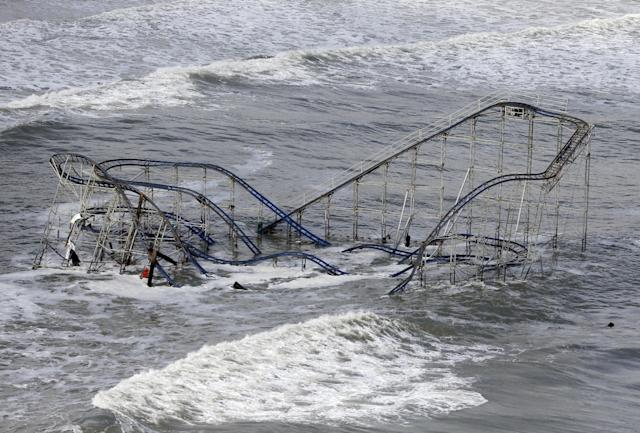 """FILE - In this Wednesday, Oct. 31, 2012 file photo, waves wash over a roller coaster from a Seaside Heights, N.J. amusement park that fell in the Atlantic Ocean during superstorm Sandy. Though it's tricky to link a single weather event to climate change, Hurricane Sandy was """"probably not a coincidence"""" but an example of extreme weather events that are likely to strike the US more often as the world gets warmer, the U.N. climate panel's No. 2 scientist told the Associated Press Tuesday, Nov. 27, 2012.(AP Photo/Mike Groll, File)"""