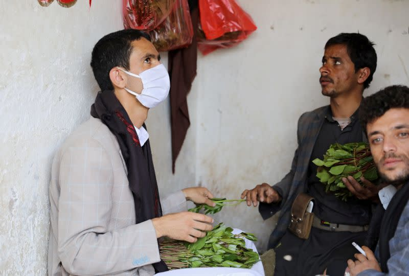 Customer wearing a protective face mask buys qat, a mild stimulant, at a qat market amid concerns of the spread of the coronavirus disease (COVID-19) in Sanaa