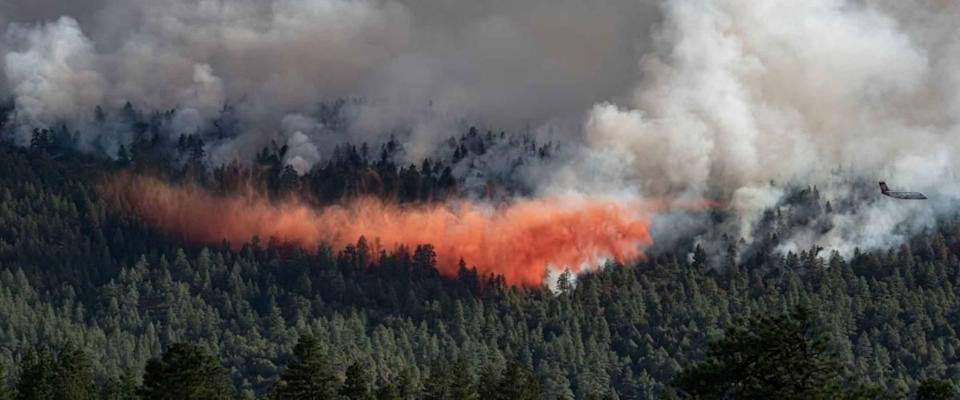An air tanker plane releases fire retardant on a forest fire in Lumberton, New Mexico, on May 10, 2020.