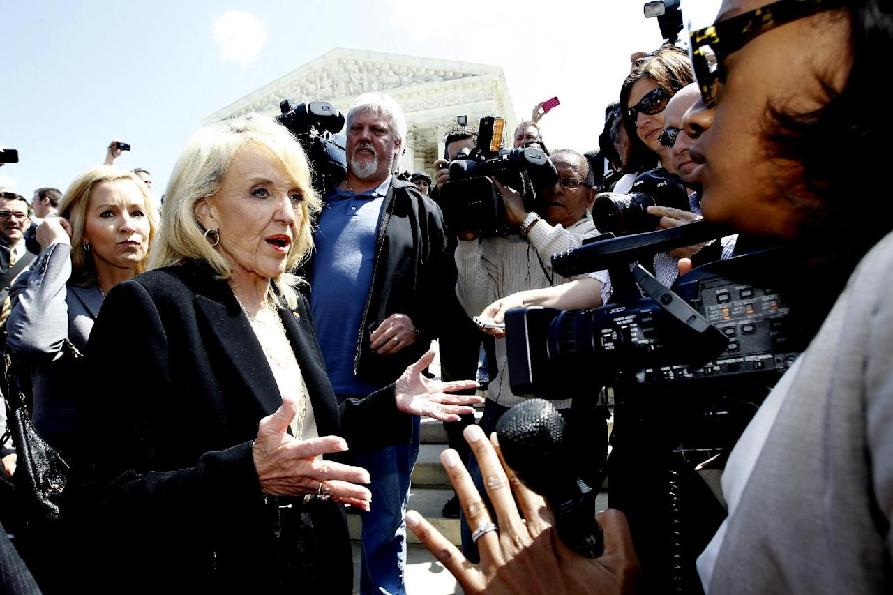 "Arizona Gov. Jan Brewer speaks to reporters outside the Supreme Court in Washington, Wednesday, April 25, 2012, after the court's hearing on Arizona's ""show me your papers"" immigration law. (AP Photo/Charles Dharapak)"