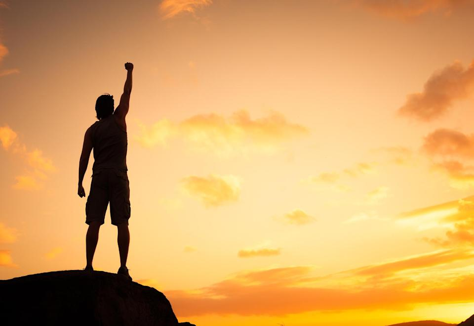 The silhouette of a man with his arm raised in celebration.