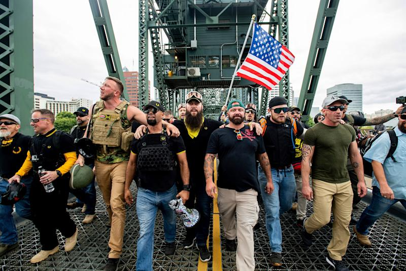 Members of the Proud Boys and other right-wing demonstrators march across the Hawthorne Bridge during a rally in Portland, Oregon, on Aug. 17, 2019. The group includes organizer Joe Biggs (in green hat) and Proud Boys Chairman Enrique Tarrio (holding megaphone). (Photo: ASSOCIATED PRESS)