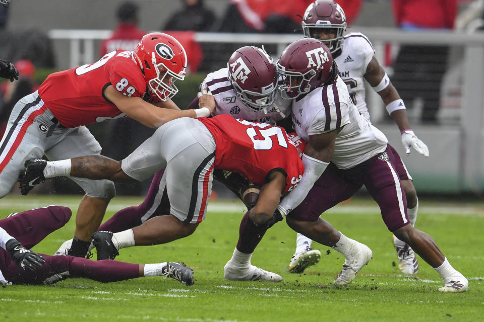 Nov 23, 2019; Athens, GA, USA; Texas A&M Aggies defensive lineman DeMarvin Leal (8) and linebacker Buddy Johnson (1) tackle Georgia Bulldogs running back Brian Herrien (35) during the first quarter at Sanford Stadium. Mandatory Credit: Dale Zanine-USA TODAY Sports