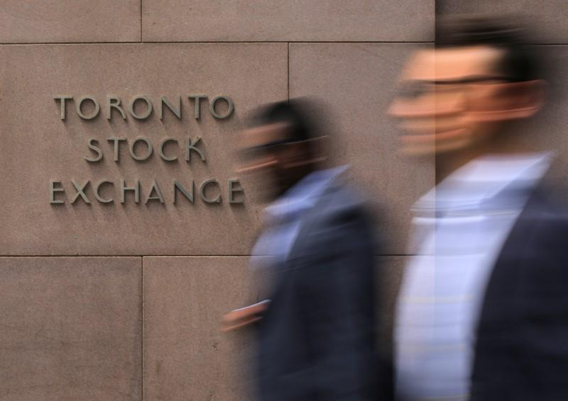 Businessmen pass the Toronto Stock Exchange sing in Toronto