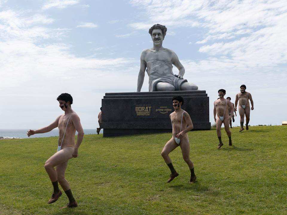 Not so very nice: The dubious Borat statue surrounded by performers in Bondi, SydneyGetty Images