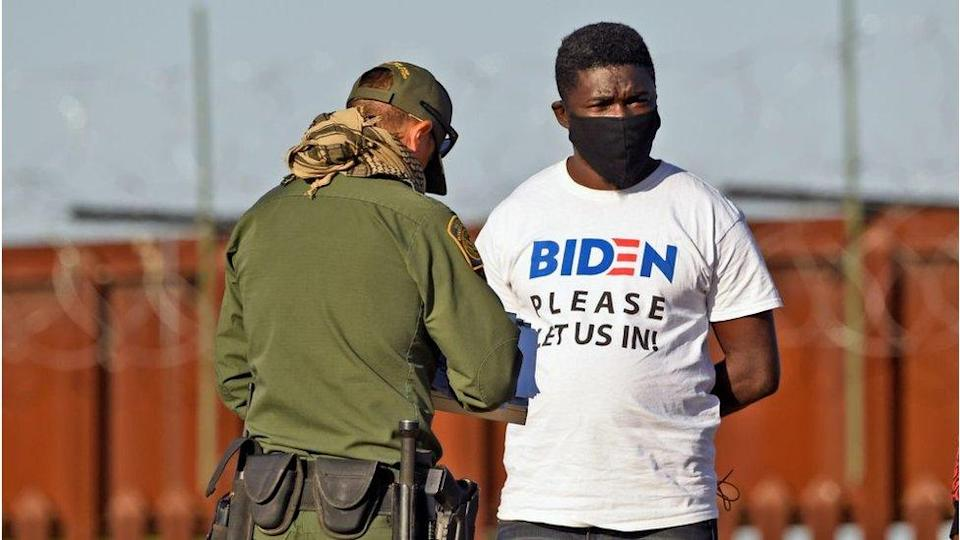 """A man detained in Arizona wears a t-shirt saying """"please let us in"""""""