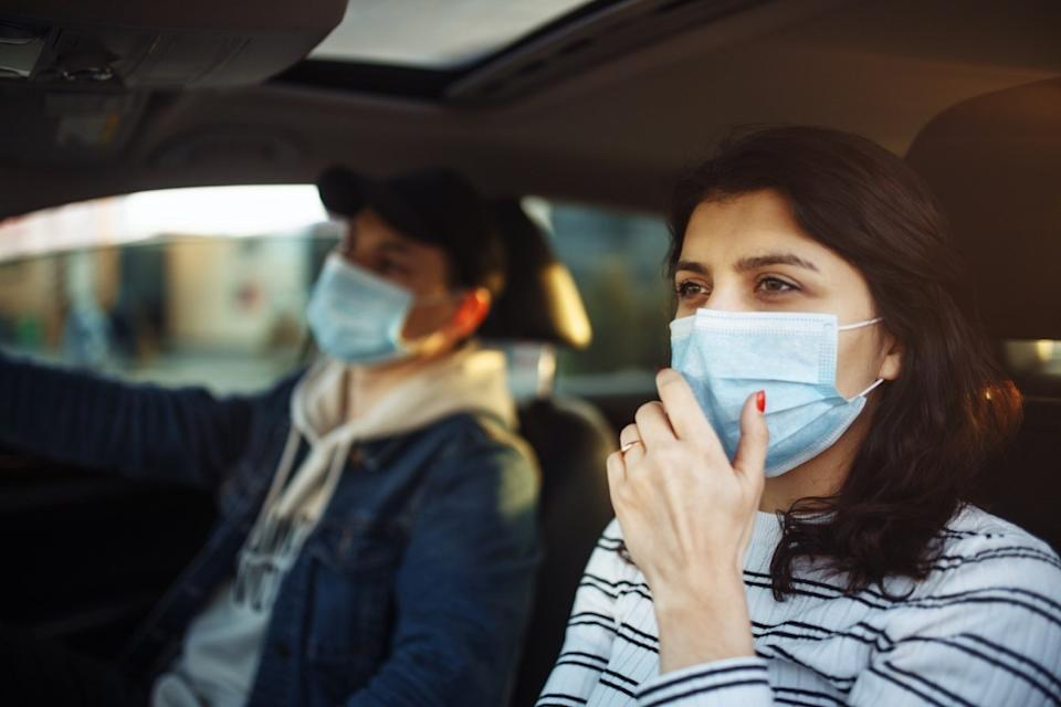 woman wearing mask coughing into hand