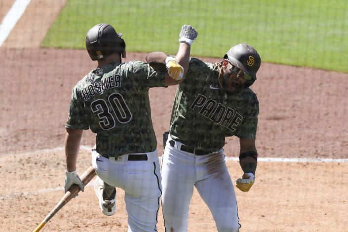 San Diego Padres' Fernando Tatis Jr., right, celebrates with Eric Hosmer (30) after hitting a grand slam off Seattle Mariners relief pitcher Robert Dugger in the seventh inning of a baseball game Sunday, May 23, 2021, in San Diego. (AP Photo/Derrick Tuskan)