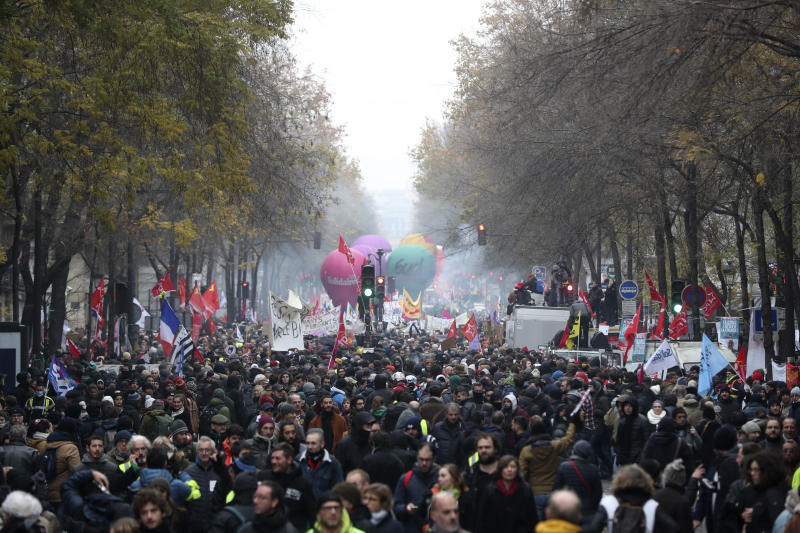 People march during a demonstration in Paris, Thursday, Dec. 5, 2019. The Eiffel Tower shut down, France's vaunted high-speed trains stood still and several thousand protesters marched through Paris as unions launched open-ended, nationwide strikes Thursday over the government's plan to overhaul the retirement system. (AP Photo/Thibault Camus)