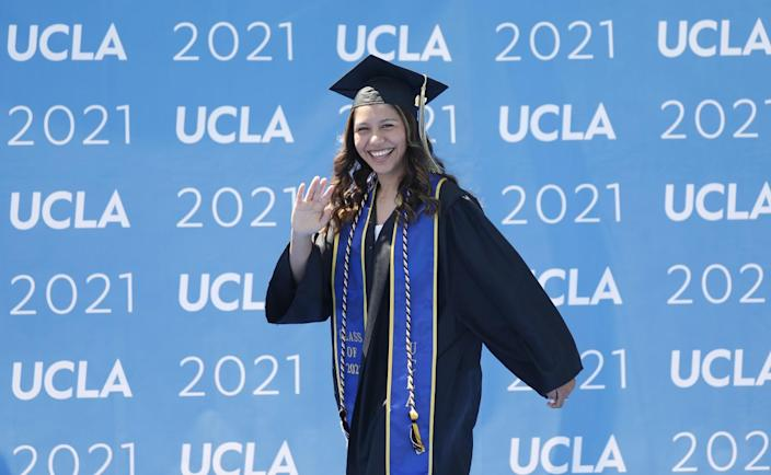Graduating with a degree in biology and Chicana/o Studies, Jennifer Bribiesca waves to her family.