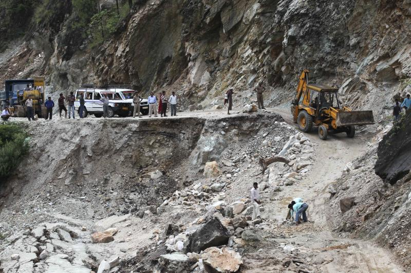 Local authorities clear a damaged road caused by landslides, in Gauchar, in northern Indian state of Uttarakhand, Tuesday, June 25, 2013. Home Minister Sushikumar Shinde told reporters that the death toll from landslides and monsoon floods will exceed the figure of 1,000 given Sunday by the Uttarakhand government. More bodies were being found as troops and disaster rescue teams cleared debris from buildings and houses destroyed by flood waters, Shinde said. (AP Photo/Rafiq Maqbool)