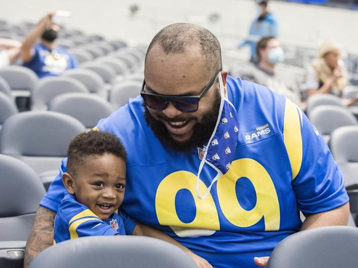 Rams season ticket holder Christian Paris, right, and son Harper Paris, tour SoFi Stadium in Inglewood on Saturday.