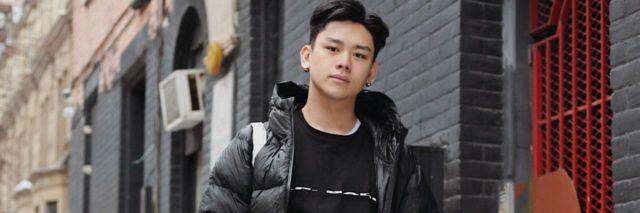 photo of young asian man standing in street with hands in pockets and looking at camera