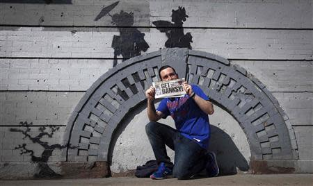 A man holds up a local newspaper as he poses for a photo in front of a new art piece by British graffiti artist Banksy in the Brooklyn borough of New York, October 17, 2013. REUTERS/Carlo Allegri