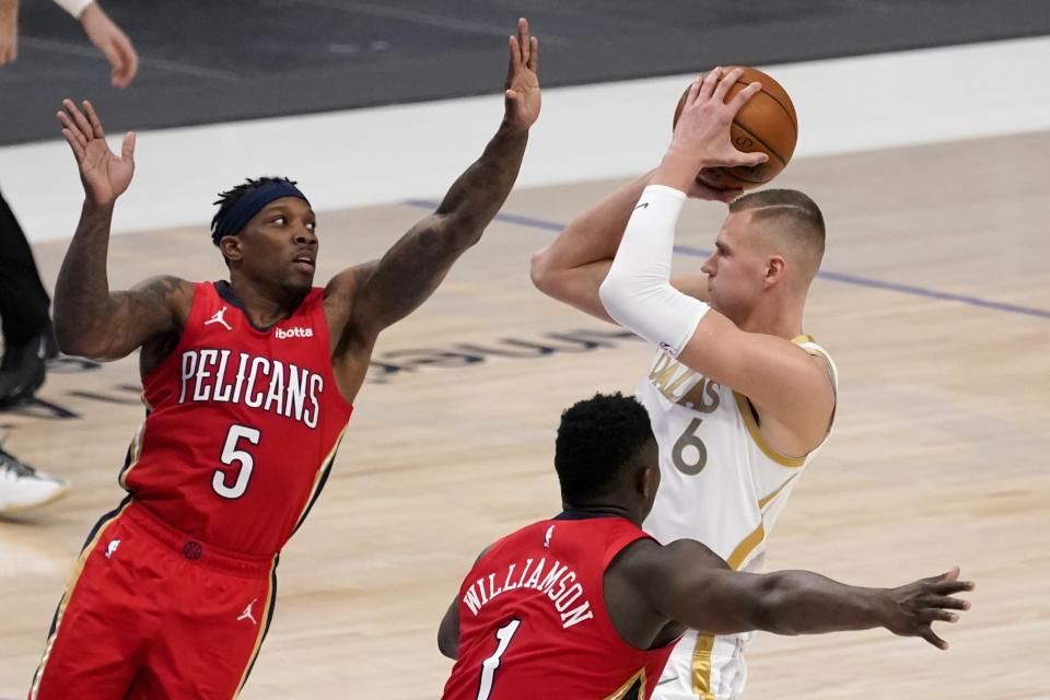 New Orleans Pelicans' Eric Bledsoe (5) and Zion Williamson (1) defend as Dallas Mavericks' Kristaps Porzingis (6) shoots during the first half of an NBA basketball game in Dallas, Friday, Feb. 12, 2021. (AP Photo/Tony Gutierrez)