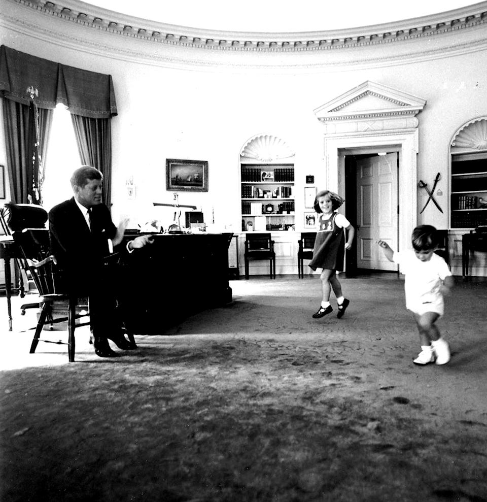 <p>President John F. Kennedy claps while his son John Jr. and daughter Caroline play in the Oval Office in October 1962.</p>