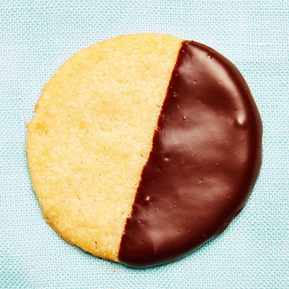 """<strong>Elizabeth's Christmas Cookies</strong><br>Adapted from <a href=""""http://cooking.nytimes.com/recipes/1017031-chocolate-mint-thins-with-candy-cane-crunch"""" rel=""""nofollow noopener"""" target=""""_blank"""" data-ylk=""""slk:this"""" class=""""link rapid-noclick-resp"""">this</a> <em>NYT</em> recipe<br>Yield: About 5 dozen<br><br><strong>Elizabeth Kiefer:</strong> <em>""""Every year, my girlfriends have a holiday cookie decorating party in Brooklyn and vote on our favorite recipe from the afternoon (based on ample taste testing, obviously). This one has yet to be knocked out of the top spot!""""</em><br><br><strong>Ingredients</strong><br><em>For the cookies:</em><br>1 cup sugar<br> 12 tbsp butter<br>1/2 tsp salt<br>1 egg<br>1 1/2 cup flour<br>1 tsp extract — baker's choice! Sometimes I use vanilla or almond, or if I'm feeling crazy I might even go with orange.<br><br><em>For the chocolate coating:</em><br>Everyone please acquire a double boiler like an adult and don't try and put one pan in another pan full of boiling water (learn from my Cookie Debacle of 2012. It was <em>no bueno</em>.)<br>2 (8 oz) bars of baking chocolate<br>2 tbsp coconut oil (melted down, but go easy on the oil)<br><br><strong>Instructions</strong><br>1. Cream sugar and butter in a food processor.<br><br>2. Add in the salt, egg, and flour. Mix well to combine. If the dough cracks, you can add up to 1 tablespoon of water, but consider what your radiator is up to, because if it's super dry in your apartment, who knows, you might need more.<br><br>3. Roll out the dough until it is very thin on parchment-lined cookie sheets and refrigerate for at least 4 hours (and up to 1-2 days).<br><br>4. Once dough is chilled and set, use a circular cookie cutter to make cookie shapes. Set aside on parchment-lined baking sheet, about one inch apart.<br><br>5. Bake at 350ºF for 10-12 minutes.<br><br>6. Meanwhile, make your chocolate coating: Melt the chocolate. When cookies are done baking and cooled, dip the cookies about halfway. (Ski"""