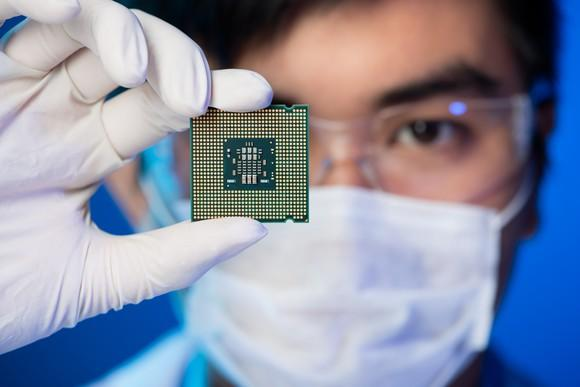 Worker wearing a mask and gloves looking at a semiconductor chip.