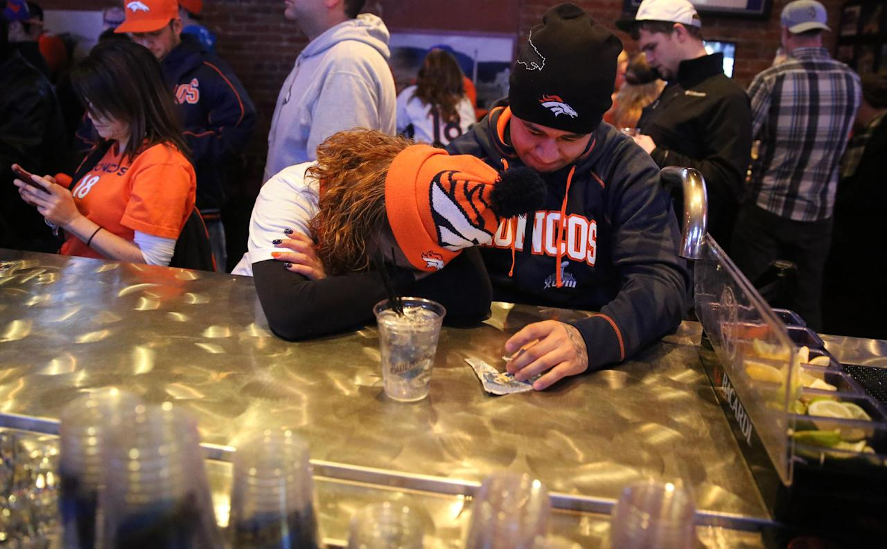 Denver Broncos fans Tatiana Bohorquez and Jorge Puerto look away from the TV while watching their team fall behind the Seattle Seahawks during the second half of the Super Bowl, inside Jackson's, a sports bar and grill in Denver, Sunday, Feb. 2, 2014. The Seahawks won 43-8. (AP Photo/Brennan Linsley)
