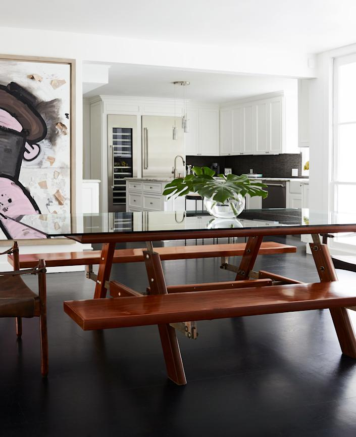 "<div class=""caption""> The breakfast nook near the kitchen is furnished with Sergio Rodrigues's Picnic table from the 1970s, made of hardwood, metal, and glass. Jorge Zalszupin's Veranda chairs from the 1960s, with jacarandá frames and adjustable leather straps, complete the vintage look. The artwork on the back wall is by American artist Carroll Dunham (actress Lena Dunham's father). </div>"