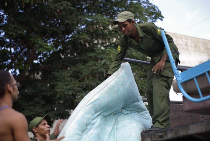 Soldiers and civilians unload mattresses and bed frames to a shelter as they prepare for the arrival of Tropical Storm Isaac in Siboney, Cuba, Friday, Aug. 24, 2012. Tropical Storm Isaac strengthened slightly as it spun toward the Dominican Republic and vulnerable Haiti on Friday, threatening to bring punishing rains but unlikely to gain enough steam to strike as a hurricane. Cuba declared a state of alert Friday for six eastern provinces. (AP Photo/Ramon Espinosa)