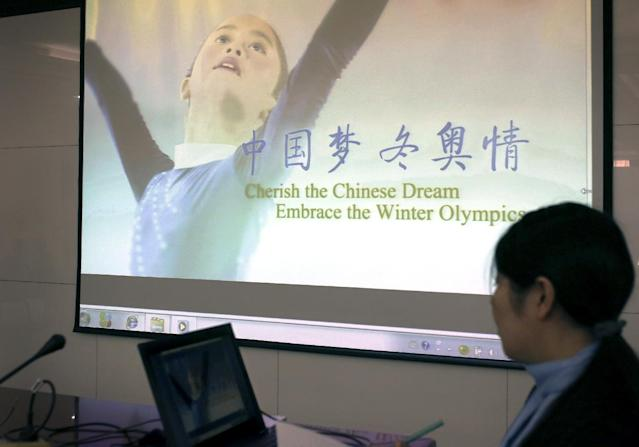 A worker plays a short video promoting Beijing's bid for the 2022 Winter Olympics during a media briefing by Chinese officials, at the Beijing Olympics Headquarters in Beijing, China Tuesday, Nov. 4, 2014. The new front-runner to host the 2022 Winter Olympics doesn't have a long winter sports tradition. Just 20 years ago, there were fewer than 10,000 skiers in China - out of a then-population of 1.2 billion. (AP Photo/Andy Wong)