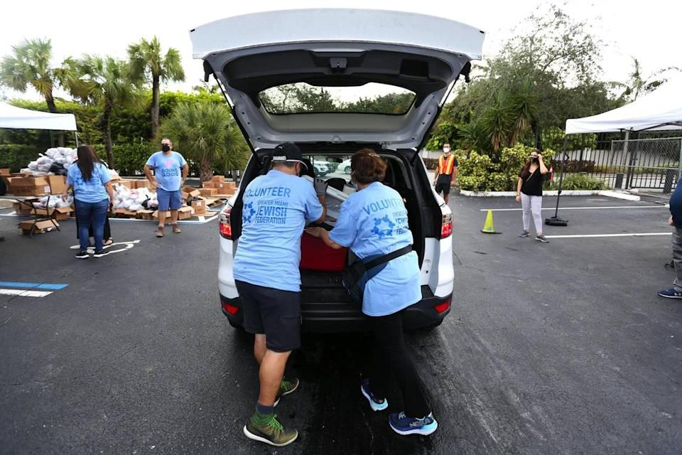 Volunteers load the trunk of an SUV with bags of food during a kosher food distribution event at the Greater Miami Jewish Federation parking lot in response to widespread economic hardship and food insecurity brought on by the COVID-19 pandemic, in Miami, Florida Friday, October 16, 2020.
