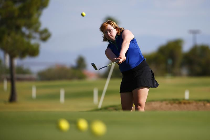 In this Aug. 28, 2019, photo, Amy Bockerstette practices with her teaching pro at Palmbrook Country Club on Wednesday, Aug. 28, 2019, in Sun City, Ariz. When Bockerstette arrived at the Phoenix Open's 16th hole in late January believing she was there to meet Gary Woodland during a practice round. When the diminutive 20-year-old in the purple shirt and white skirt got up and down for par from a greenside bunker, it sent reverberations beyond the golf-hole-turned-stadium. (AP Photo/Ross D. Franklin)
