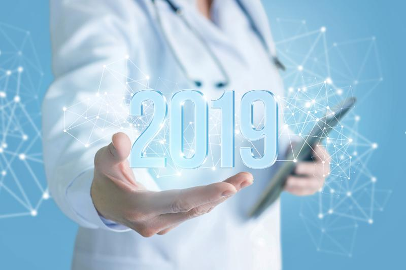 Physician holding a table in one hand and the other hand extended with an image of 2019 appearing over her hand surrounded by points of light connected by lines