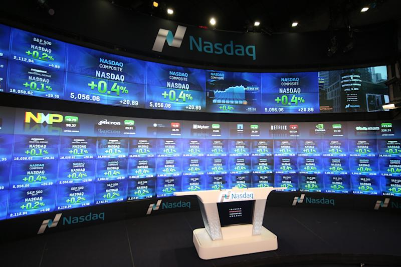 An indoor television studio at the Nasdaq exchange, complete with the electronic big board in the background.