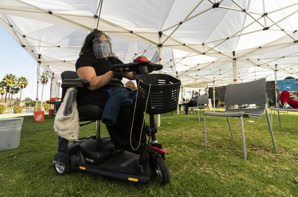 Veronica Lopez, 42, who has Spina bifida, wears a face shield and mask as she waits at the recovery tent for 15 minutes after being vaccinated at the St. John's Well Child and Family Center's COVID-19 vaccination site at the East Los Angeles Civic Center in Los Angeles, Thursday, March 4, 2021. California will begin setting aside 40% of all vaccine doses for the state's most vulnerable neighborhoods in an effort to inoculate people most at risk from the coronavirus more quickly. (AP Photo/Damian Dovarganes)