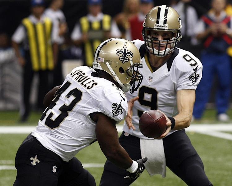 New Orleans Saints quarterback Drew Brees (9) hands off to running back Darren Sproles on a touchdown carry in the first half of an NFL football game in New Orleans, Monday, Sept. 30, 2013. (AP Photo/Bill Haber)