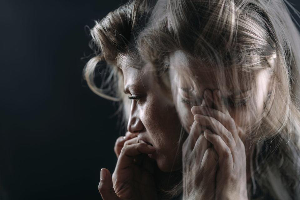 A double exposure of a woman with her hands in front of her mouth.