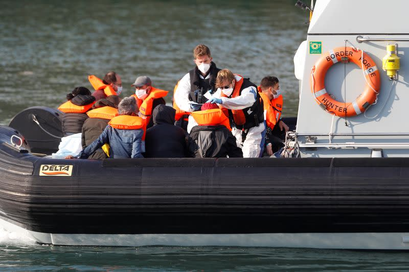 Border Force crew attend migrants in a Border Force boat at Dover harbour