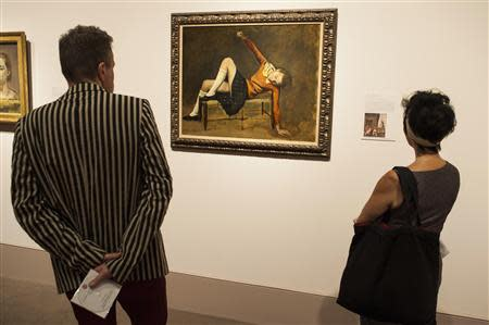 """A woman looks at the painting entitled """"Therese on a bench seat"""" by French artist Balthus at the Metropolitan Museum of Art's """"Balthus: Cats and Girls Paintings and Provocations"""" exhibition in New York"""