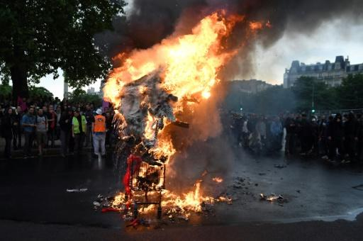 Demonstrators burned an effigy of President Emmanuel Macron during the protests in Paris on Tuesday
