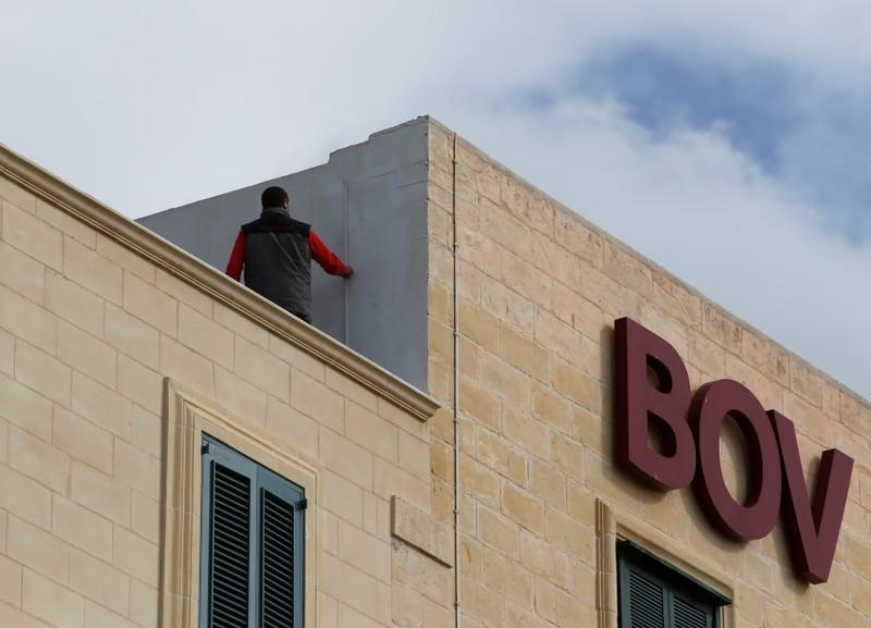 FILE PHOTO: A maintenance worker carries out repairs on the roof of a branch of Bank of Valletta in Valletta