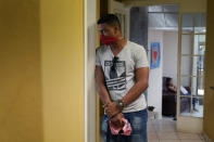 A man waits for a family member being seen at a clinic that serves asylum seekers in Matamoros, Mexico, Tuesday, Nov. 17, 2020. A humanitarian organization led by U.S. military veterans has treated thousands of migrants over the past year at two clinics in a Mexican town across the border from Texas. But Global Response Management is attempting to go beyond mere crisis response and build a system to make it easier to track the health of migrants along their journey from Central America. The efforts are part of a growing trend in humanitarian aid that has accelerated amid the coronavirus pandemic, which has highlighted the difficulties of getting basic health care to migrants. (AP Photo/Eric Gay)