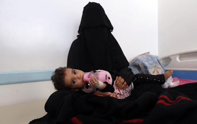 <p>A Yemeni mother holds her child suspected of being infected with cholera at a makeshift hospital in Sana'a on June 9, 2017.<br> Yemen is descending into total collapse, its people facing war, famine and a deadly outbreak of cholera, as the world watches, the UN aid chief said. (AFP/Getty Images) </p>
