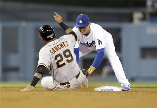 San Francisco Giants' Hector Sanchez is tagged at second by Los Angeles Dodgers shortstop Luis Cruz on a double play in the fourth inning of a baseball game in Los Angeles Wednesday, April 3, 2013. (AP Photo/Reed Saxon)