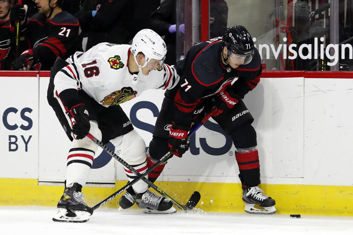 Carolina Hurricanes' Jesper Fast (71) and Chicago Blackhawks' Nikita Zadorov (16) battle along the boards during the second period of an NHL hockey game in Raleigh, N.C., Monday, May 3, 2021. (AP Photo/Karl B DeBlaker)
