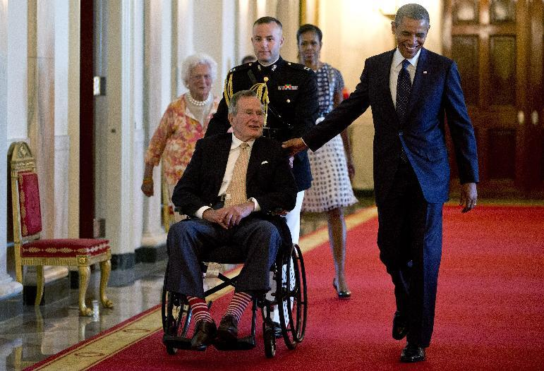 """President Barack Obama with former President George H. W. Bush, first lady Michelle Obama and former first lady Barbara Bush, behind left, arrive to present the 5,000th Daily Point of Light Award to Floyd Hammer and Kathy Hamilton, a retired couple and farm owners from Union, Iowa, in the East Room of the White House in Washington, Monday, July 15, 2013. Obama welcomed Bush to the White House in a salute to public service and to the drive for volunteerism that the 41st president inspired with his """"thousand points of light"""" initiative more than two decades ago. (AP Photo/Carolyn Kaster)"""