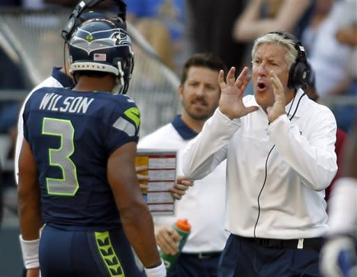 Seattle Seahawks head coach Pete Carroll, right, calls out to quarterback Russell Wilson (3) in the second half of an NFL football game against the Dallas Cowboys, Sunday, Sept. 16, 2012, in Seattle. The Seahawks won 27-7. (AP Photo/John Froschauer)