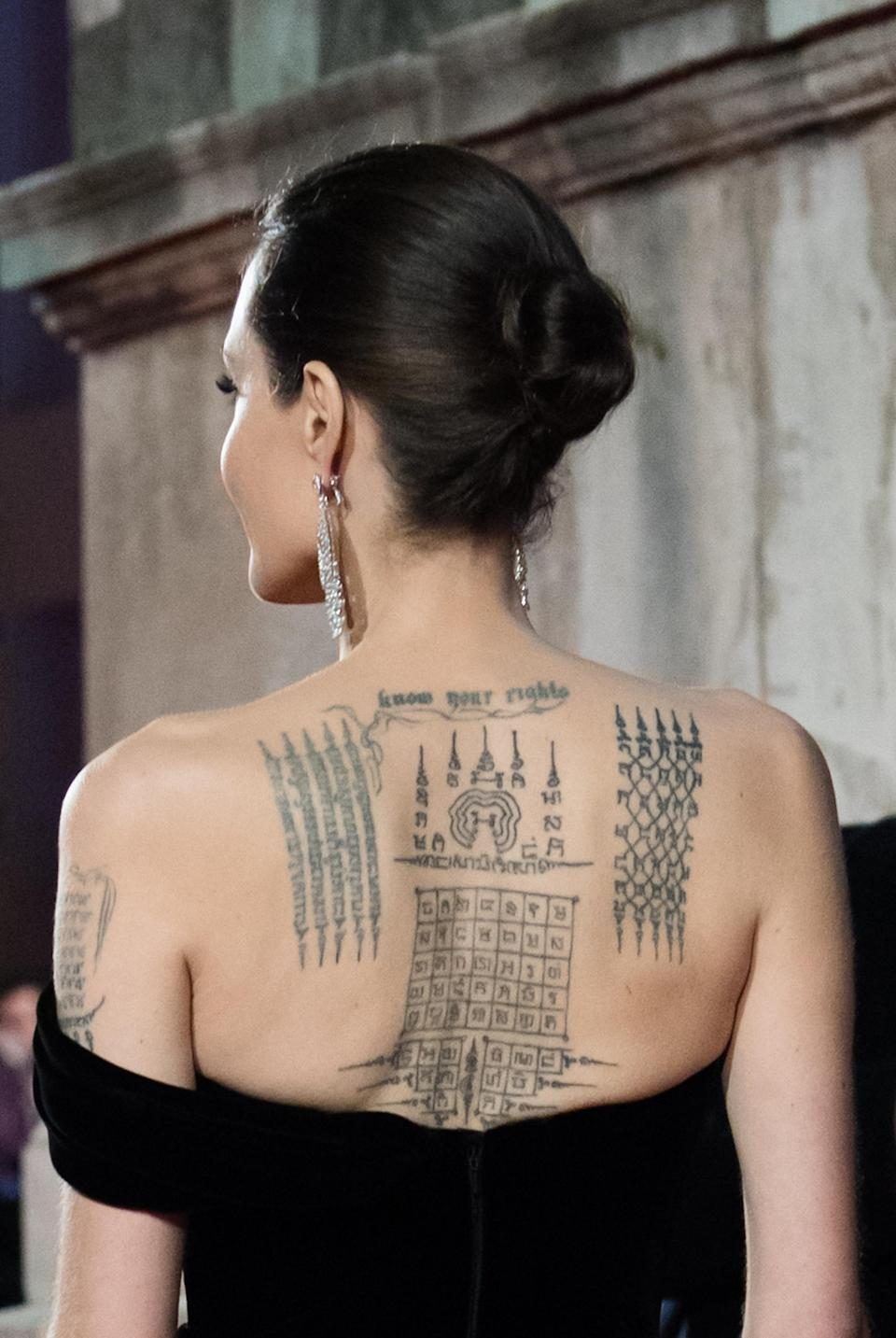<p>Actress Angelina Jolie's most famous tattoo is a Yant ViHan Pha Chad Sada ink on her back. The tattoo was created for her by Ajarn Noo Kanpai and was applied by an ex-monk using steel rods mounted with a surgical steel needle. <em>[Photo: Getty]</em> </p>