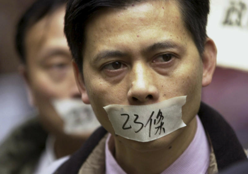 """FILE - In this photo taken Friday, Feb. 14, 2003, demonstrators with tape over their mouth with the words """"Article 23"""" turned out to protest against Hong Kong's anti-subversion bill that they say will wreck local civil liberties. The first major ripple to test the """"one country, two systems"""" framework came when Hong Kong's leaders introduced legislation that would forbid acts of """"treason"""" and """"subversion"""" against the Chinese government. (AP Photo/Anat Givon, File)"""