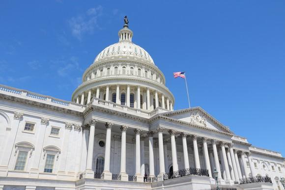 U.S. Capitol, Washington, D.C., from an angle with a heavy wind showing the U.S. flag prominently.