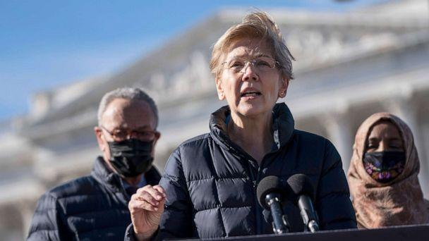PHOTO: Flanked by Senate Majority Leader Chuck Schumer and Rep. Ilhan Omar, Sen. Elizabeth Warren speaks during a press conference about student debt outside the Capitol, Feb. 4, 2021. (Drew Angerer/Getty Images)